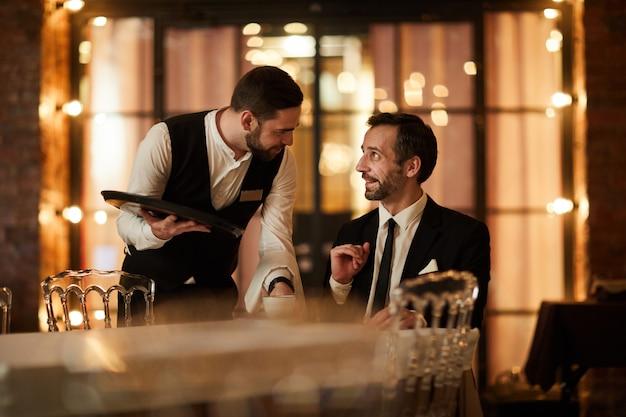 Улыбающийся бизнесмен, говорить с официантом в ресторане