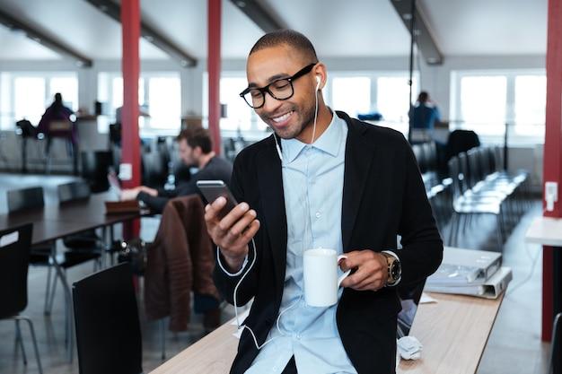 Улыбающийся бизнесмен отправляет текстовое сообщение на смартфон и держит чашку в офисе