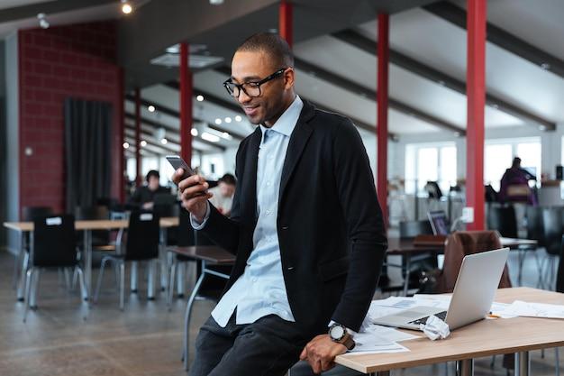 Улыбающийся бизнесмен текстовых сообщений на смартфоне в офисе