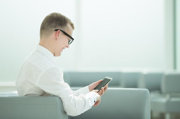 Улыбающийся бизнесмен, набрав sms на своем смартфоне