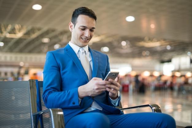 Smiling businessman using his mobile phone