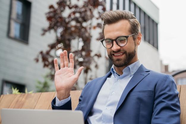 Улыбающийся бизнесмен с помощью ноутбука, имеющего видеозвонок, приветствие общение онлайн видеоконференция