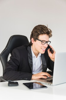 Smiling businessman using laptop while talking on smartphone