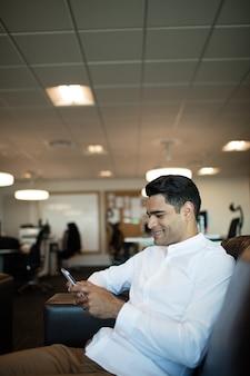 オフィスに座っている間携帯電話を使用して笑顔の実業家