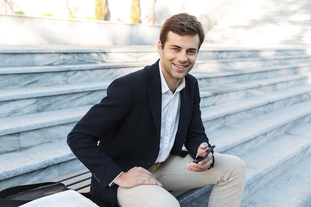 외부 단계에 앉아있는 동안 휴대 전화를 사용하여 웃는 사업가