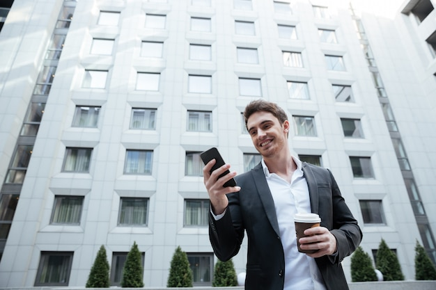 Smiling businessman with coffee using smartphone in business center