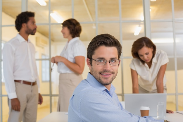 Smiling businessman with colleagues in meeting