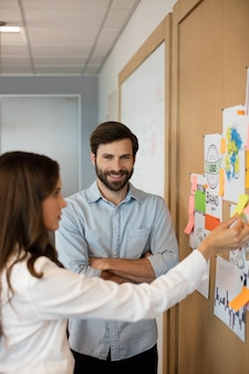 Smiling businessman with female colleague analyzing charts at office