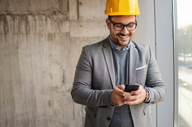 Smiling businessman with helmet on head standing next to a window in building in construction process and using phone.