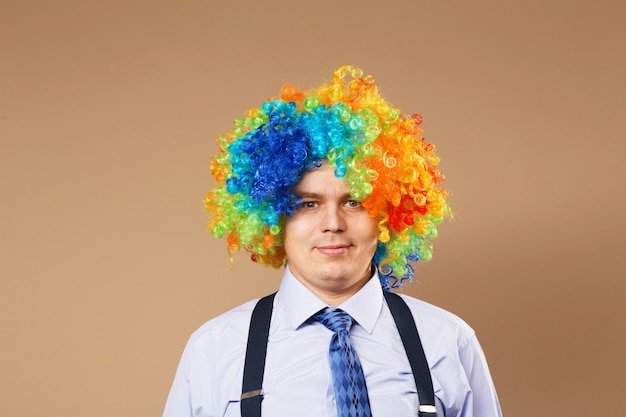Smiling businessman with large colorful wig. close-up portrait of business man in clown wig. business concept