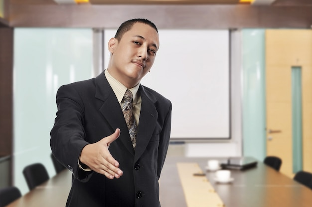 Smiling businessman with open hand ready to hand shake
