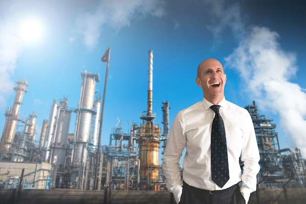Smiling businessman with behind a refinery