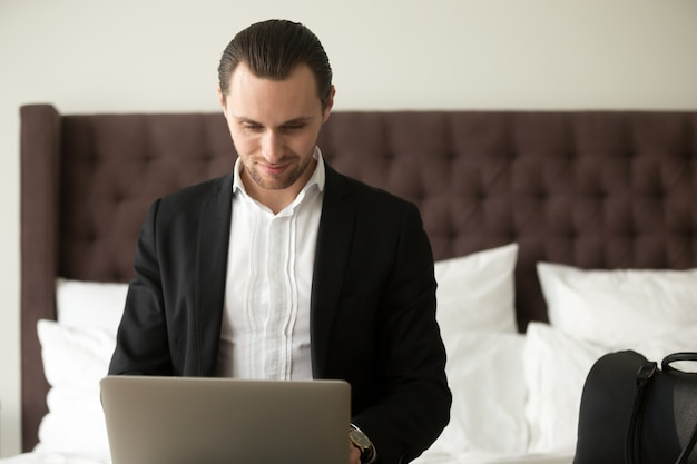 Smiling businessman working on laptop in bedroom.