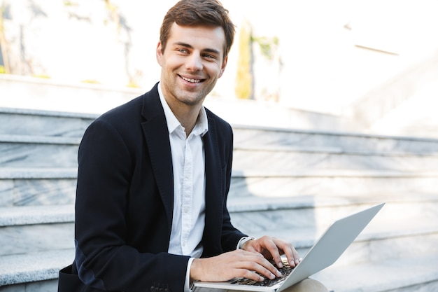 야외에서 노트북 컴퓨터에서 작업하는 웃는 사업가