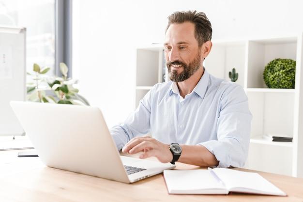 Улыбающийся бизнесмен, работающий на портативном компьютере