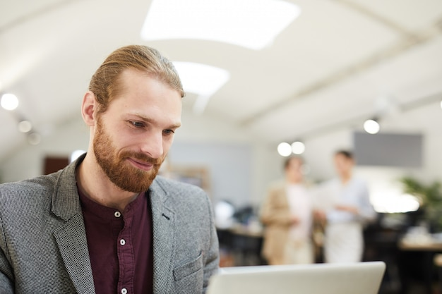 Smiling businessman working in open space office
