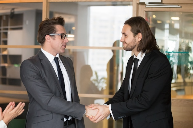 Smiling businessmen shaking hands, making deal, gratitude or promotion concept