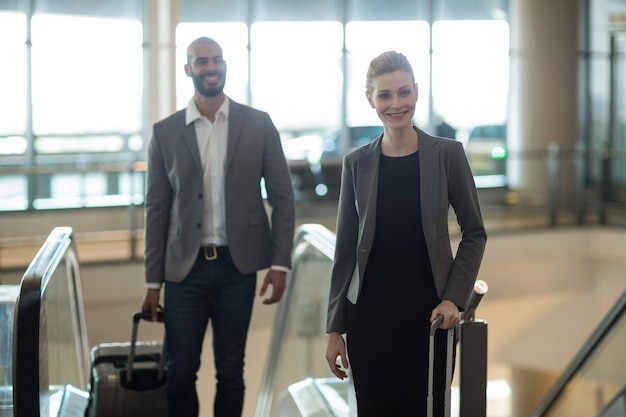 Smiling businesspeople with luggage standing in front of an escalator