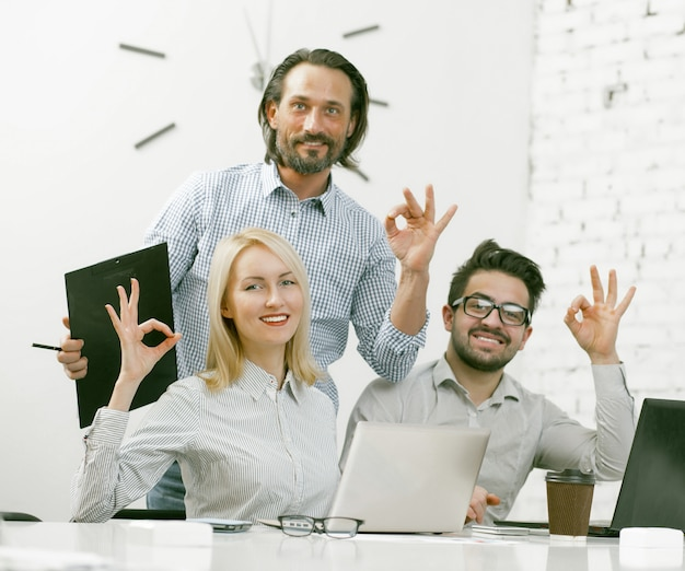 Smiling businessteam showing ok gestures in office