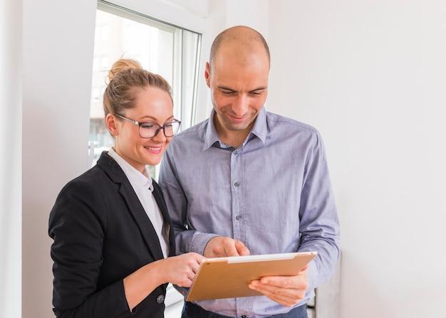 Donna di affari ed uomo d'affari sorridenti che esaminano compressa digitale