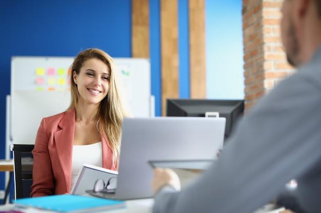 Улыбающаяся деловая женщина общается со своим коллегой-мужчиной на работе