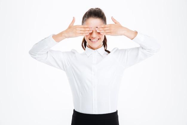 Улыбающаяся деловая женщина закрыла глаза руками над белой стеной