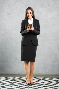 Smiling businesswoman doing text message on smartphone against concrete wall