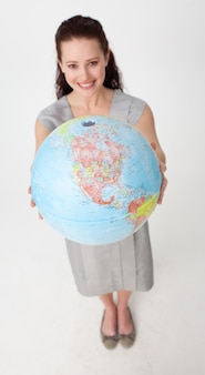 Smiling businesswoman holding a terrestrial globe