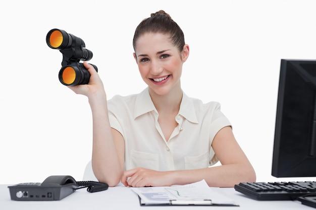 Smiling businesswoman holding binoculars
