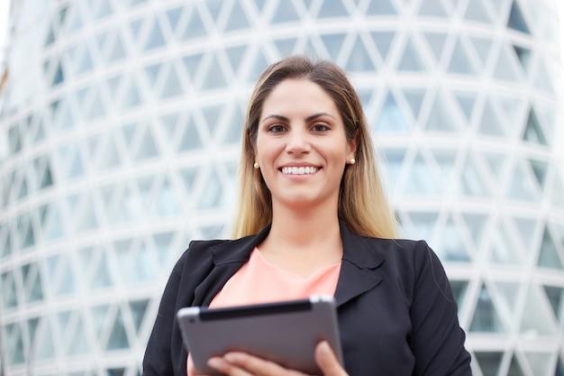 都市環境でデジタルタブレットを保持している実業家の笑顔