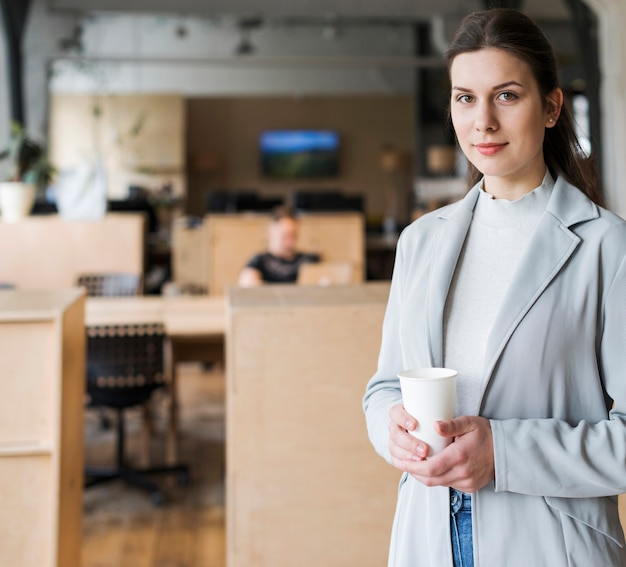 Smiling businesswoman holding disposable coffee cup in workplace
