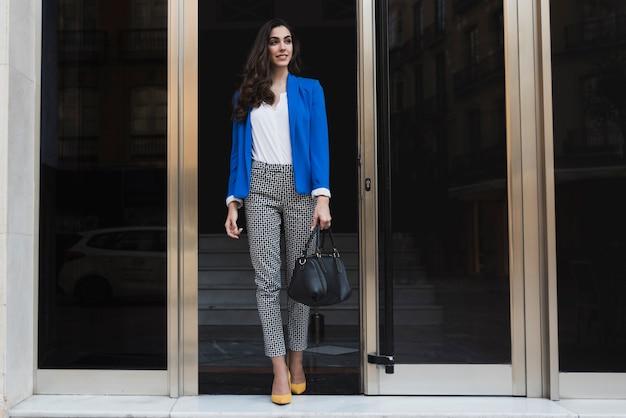 Smiling businesswoman holding her handbag in the vestibule