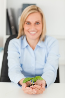 Smiling businesswoman holding a little green plant looking into camera