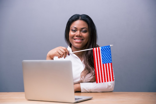 Smiling businesswoman holding us flag