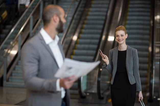 Улыбаясь бизнесвумен, взаимодействуя с бизнесменом в зоне ожидания
