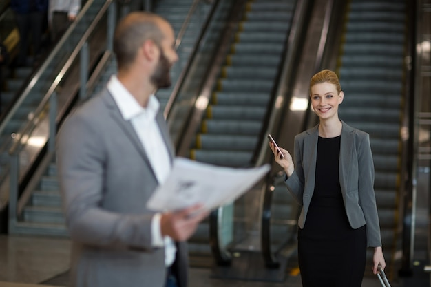 Donna di affari sorridente che interagisce con l'uomo d'affari nella zona di attesa