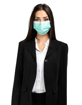 Smiling businesswoman isolated on white wearing a mask, coronavirus concept