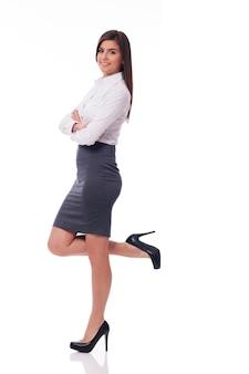 Donna di affari sorridente che si appoggia su qualcosa