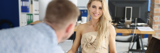 Улыбающаяся деловая женщина слушает бизнес-отчет от коллеги