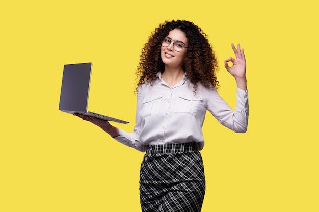 노트북 컴퓨터를 들고 노란색 배경 위에 절연 확인 손가락 제스처를 보여주는 흰 셔츠에 웃는 사업가