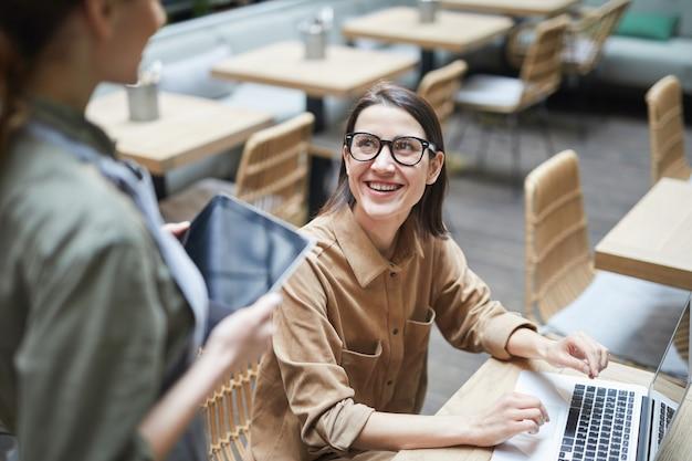 Улыбающаяся деловая женщина заказывает кофе в кафе