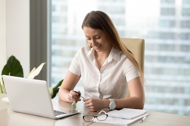 La pittura sorridente della donna di affari inchioda in ufficio