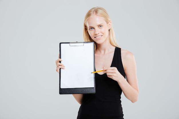 흰색 배경에 고립 된 빈 클립 보드를 가리키는 웃는 사업가