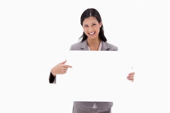 Smiling businesswoman pointing at blank sign board