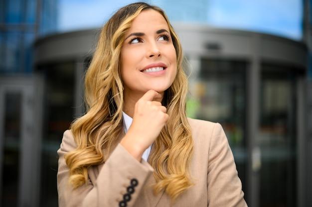 Smiling businesswoman poirtrait in a pensive expression