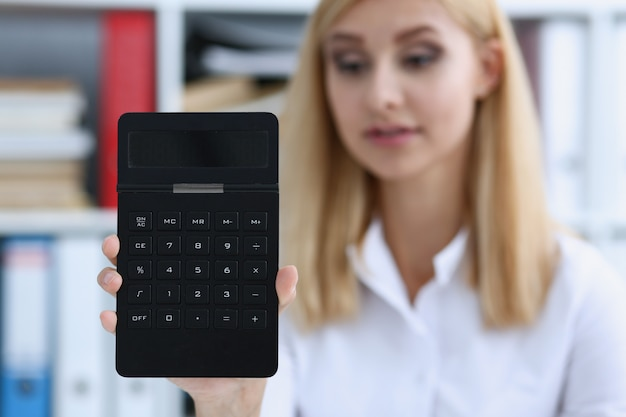 Smiling businesswoman portrait holds calculator in hand