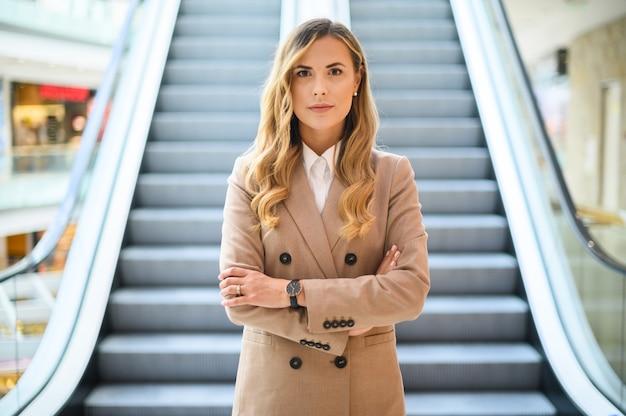 Улыбающийся портрет деловой женщины перед мобильной лестницей
