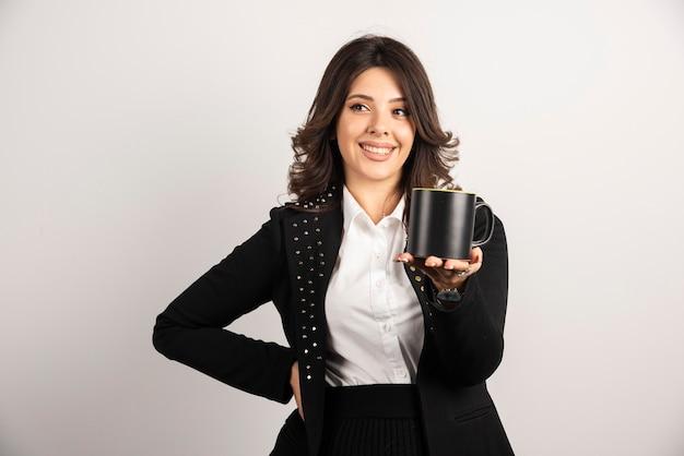 Sorridente imprenditrice in posa con il tè su bianco