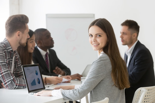 Smiling businesswoman professional or intern looking at camera at meeting