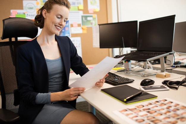 Smiling businesswoman reading document while sitting at desk